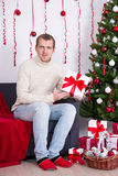 Young handsome man sitting in decorated living room with Christm Stock Images
