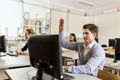 Young handsome man sitting in front of a computer raising hand Stock Photography