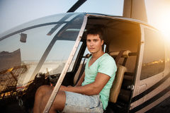 Young handsome man sitting in helicopter cockpit. Private helicopter pilot ready to fly in city on a bright sunny day Stock Photo