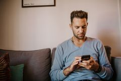 Young handsome man sitting at home on sofa and using mobile phone. Men holding smartphone hands and typing text message. Young handsome man sitting at home on royalty free stock photos