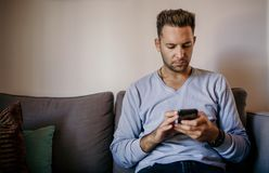 Young handsome man sitting at home on sofa and using mobile phone. Men holding smartphone hands and typing text message. Young handsome man sitting at home on royalty free stock image