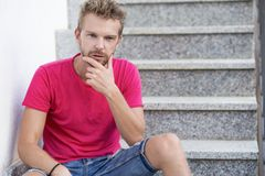 Handsome man sitting on staircase stock image