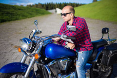 Young handsome man sitting on retro motorcycle Royalty Free Stock Image