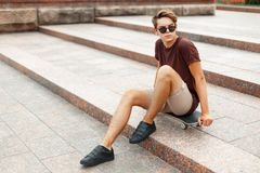 Young handsome man sitting on a skateboard. Young handsome man in sunglasses sitting on skateboard on stairway background Stock Photo