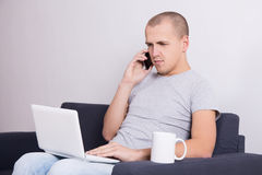 Young handsome man sitting on sofa with computer, phone and cup Royalty Free Stock Photos