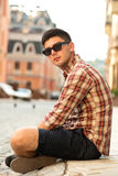 Young handsome man sitting on street. Young handsome man in sunglasses sitting on street Royalty Free Stock Images