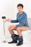 Young handsome man sitting on toilet. Royalty Free Stock Photos