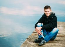 Young handsome man sitting on wooden pier Royalty Free Stock Photo
