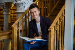 Young handsome man in traditional library. Young handsome man sitting on wooden stairs in traditional library, holding book. Beautiful interior of old library royalty free stock photo