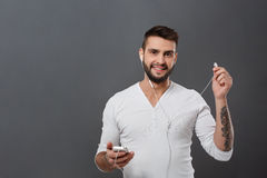 Young handsome man smiling holding phone over grey background. Stock Photography