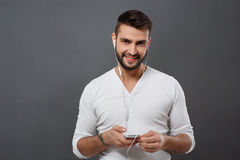 Young handsome man smiling holding phone over grey background. Royalty Free Stock Image