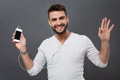 Young handsome man smiling holding phone over grey background. Royalty Free Stock Photo