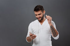Young handsome man smiling looking at phone over grey background. Royalty Free Stock Photography