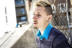 Young handsome man smoking outdoor against grunge fence Royalty Free Stock Photo