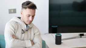 Young man speaking to smart electronic speaker home assistant. Young handsome man speaking to smart electronic speaker home assistant, sitting on couch in living stock video