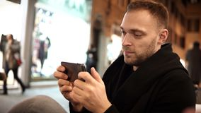 Young handsome man spending leisure time in cafe in evening and using the smartphone with touchscreen. Attractive male browsing the Internet in the city centre stock footage