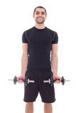 Young handsome man in sportswear doing exercises with dumbbells Stock Image