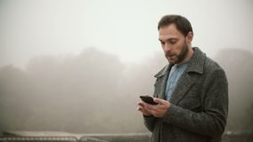 Young handsome man standing early in the foggy morning in park. Bearded male using the smartphone with touchscreen. Stylish man browsing the Internet from stock video