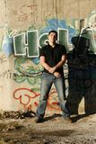 Young handsome man standing by the graffiti wall Royalty Free Stock Image