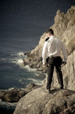 Young handsome man standing on rocks overlooking ocean. Wearing climbing gear Royalty Free Stock Photo