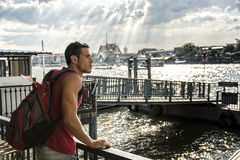 Casual man with backpack on city embankment. Young handsome man standing on seafront looking around in sunlight, Bangkok Royalty Free Stock Photos