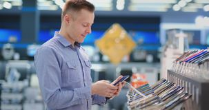 A young handsome man standing at a shop window with smartphones in a portable electronics store chooses to buy a new. Phone model. Purchase the latest version stock footage