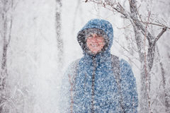 Young handsome man standing in snowfall on background of snowy forest. stock photos