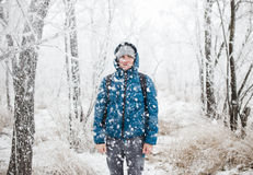 Young handsome man standing in snowfall on background of snowy forest. royalty free stock images
