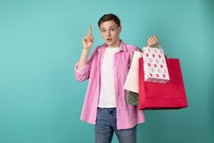 Young handsome man standing thoughtfully with shoping bags in hand. Pointing up with finger, remembered that forgot to buy a gift for his girlfriend, isolated royalty free stock image