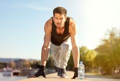 Young handsome man in start position. Ready to training royalty free stock photo