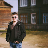 Young handsome man staying near old wooden house in autumn or sp Royalty Free Stock Photos