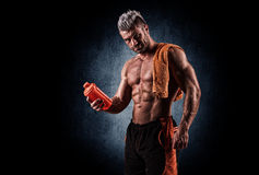Young handsome man with strong muscles, protein drink after trai Stock Photos