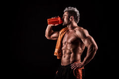 Young handsome man with strong muscles, protein drink after trai Royalty Free Stock Photos