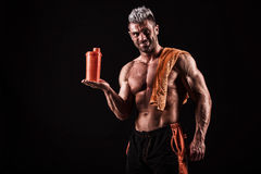 Young handsome man with strong muscles, protein drink after trai Stock Image