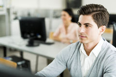 Young handsome man studying information technology in a classroo Royalty Free Stock Photography
