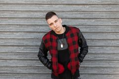 Young handsome man with a stylish hairstyle in a trendy black T-shirt in a stylish red checkered jacket with leather sleeves. With vintage amulets around the stock photo