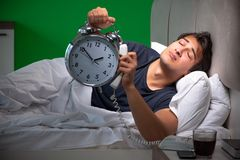 The young handsome man suffering from insomnia at home. Young handsome man suffering from insomnia at home royalty free stock image