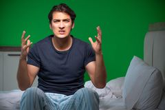 The young handsome man suffering from insomnia at home. Young handsome man suffering from insomnia at home stock photo