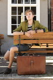 Young handsome man with suitcase waits on bench Stock Photography