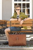 Young handsome man with suitcase waits on bench Royalty Free Stock Photography