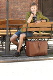 Young handsome man with suitcase waits on bench Royalty Free Stock Photo