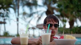Young handsome man in sunglasses drinking cocktail and eating tropical fruit in swimming pool on travel vacation. Young handsome man in sunglasses drinking stock footage