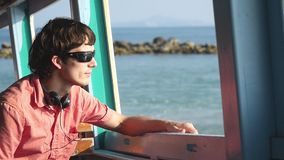 Young handsome man in sunglasses enjoying a sailing trip on the sea. Vacation concept. slow motion. 1920x1080. Young handsome man in sunglasses enjoying a stock footage