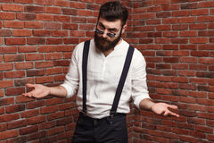 Young handsome man in sunglasses gesturing posing over brick background. Stock Photo