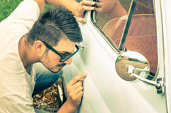 Young handsome man with sunglasses inspecting a vintage car body Royalty Free Stock Image