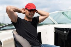 Young handsome man in sunglasses, red cap and black t-shirt in a boat royalty free stock photography