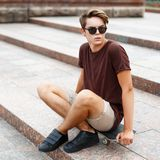 Young handsome man in sunglasses resting on a skateboard. On a summer day Stock Images