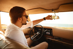 Young handsome man in sunglasses sitting inside his car stock image