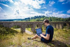 A young man sitting with laptop outdoor near old stone railway bridge Stock Photos