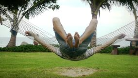 Young handsome man in sunglasses swinging on hammock next to beautiful tropical beach. slow motion. Vacation concept. 1920x1080, hd stock footage